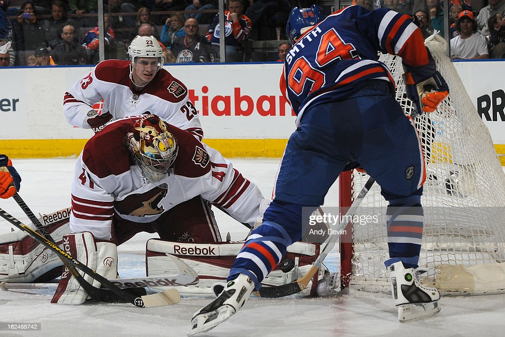 Mike Smith #41 of the Phoenix Coyotes makes a pad save on Ryan Smyth #94 of the Edmonton Oilers on February 23, 2013 at Rexall Place in Edmonton, Alberta, Canada.