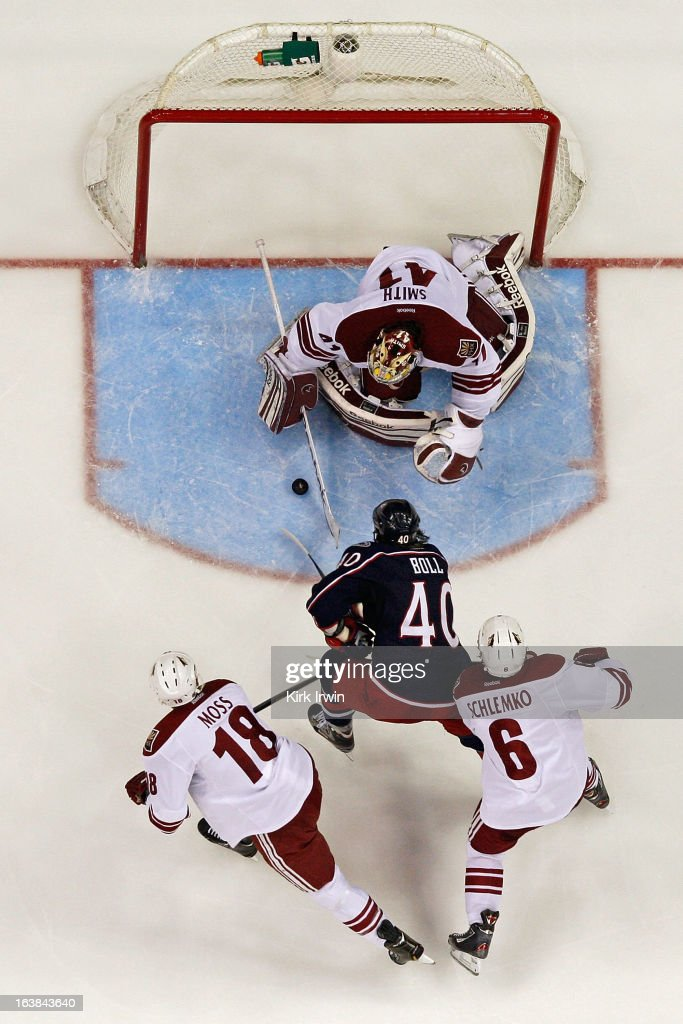 Mike Smith #41 of the Phoenix Coyotes makes a save on <a gi-track='captionPersonalityLinkClicked' href=/galleries/search?phrase=Jared+Boll&family=editorial&specificpeople=2238879 ng-click='$event.stopPropagation()'>Jared Boll</a> #40 of the Columbus Blue Jackets as he skates between David Moss #18 of the Phoenix Coyotes and <a gi-track='captionPersonalityLinkClicked' href=/galleries/search?phrase=David+Schlemko&family=editorial&specificpeople=3144738 ng-click='$event.stopPropagation()'>David Schlemko</a> #6 of the Phoenix Coyotes during the third period on March 16, 2013 at Nationwide Arena in Columbus, Ohio. Columbus defeated Phoenix 1-0 in a shootout.