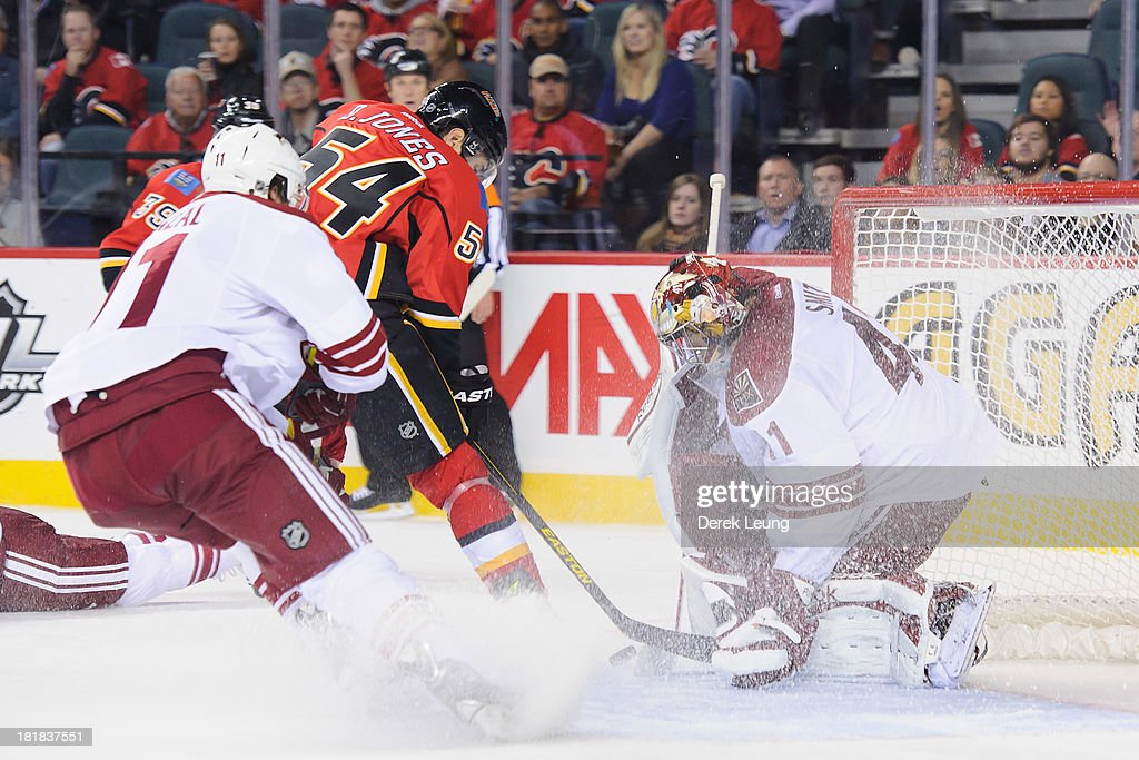 Mike Smith #41 of the Phoenix Coyotes stops the shot of David Jones #54 of the Calgary Flames during a preseason NHL game at Scotiabank Saddledome on September 25, 2013 in Calgary, Alberta, Canada.