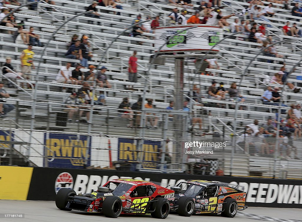 Mike Stefanik, driver of the #22 Robert B. Our Co./Canto & Sons Paving Ford leads Todd Szegedy, driver of the UNOH/Dunleavy Repair Ford to checkered flag during the NASCAR Whelen Modified Titan Roof 150 at Bristol Motor Speedway on August 21, 2013 in Bristol, Tennessee.