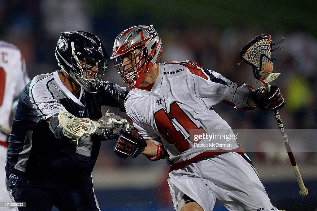 Mike Stone #41 of Boston Cannons runs past Dan Burns #4 of Chesapeake Bayhawks during a game at Navy-Marine Corps Memorial Stadium on July 18, 2013 in Annapolis, Maryland.
