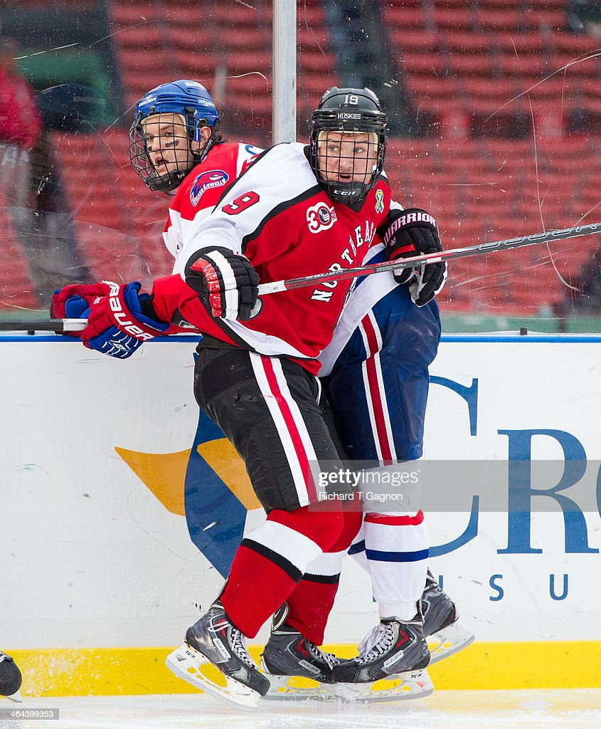 Mike Szmatula #19 of the Northeastern University Huskies checks Adam Chapie #13 of the Massachusetts Lowell River Hawks during NCAA hockey action in the 'Citi Frozen Fenway 2014' at Fenway Park on January 11, 2014 in Boston, Massachusetts.