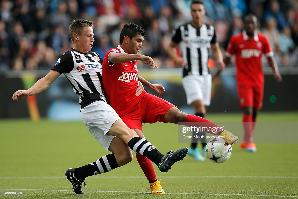 Mike te Wierik of Heracles tackles Jesus Corona of Twente during the Dutch Eredivisie match between Heracles Almelo and FC Twente at Polman Stadion on September 21, 2014 in Almelo, Netherlands.