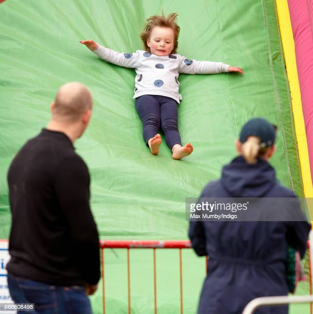 Mike Tindall and Zara Phillips look on as daughter Mia Tindall plays on an inflatable bouncy slide at the Burnham Market Horse Trials on April 14...