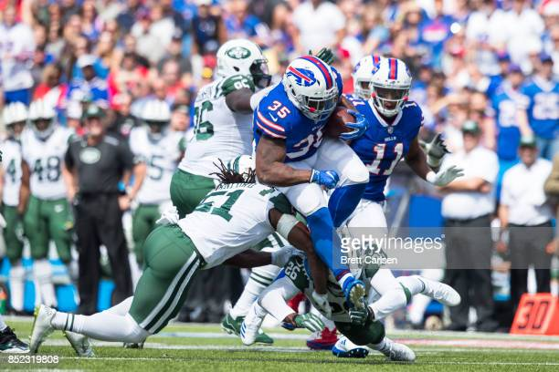 Mike Tolbert of the Buffalo Bills attempts to avoid tackles by Julian Stanford and Marcus Maye of the New York Jets during the game on September 10...
