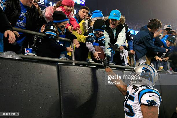 Mike Tolbert of the Carolina Panthers gives a game ball to an appreciative fan after their NFC Wild Card Playoff game against the Arizona Cardinals...