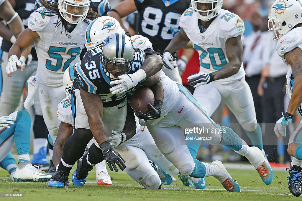 <a gi-track='captionPersonalityLinkClicked' href=/galleries/search?phrase=Mike+Tolbert&family=editorial&specificpeople=5314124 ng-click='$event.stopPropagation()'>Mike Tolbert</a> #35 of the Carolina Panthers is tackled by <a gi-track='captionPersonalityLinkClicked' href=/galleries/search?phrase=Dannell+Ellerbe&family=editorial&specificpeople=4090365 ng-click='$event.stopPropagation()'>Dannell Ellerbe</a> #59 of the Miami Dolphins on November 24, 2013 at Sun Life Stadium in Miami Gardens, Florida