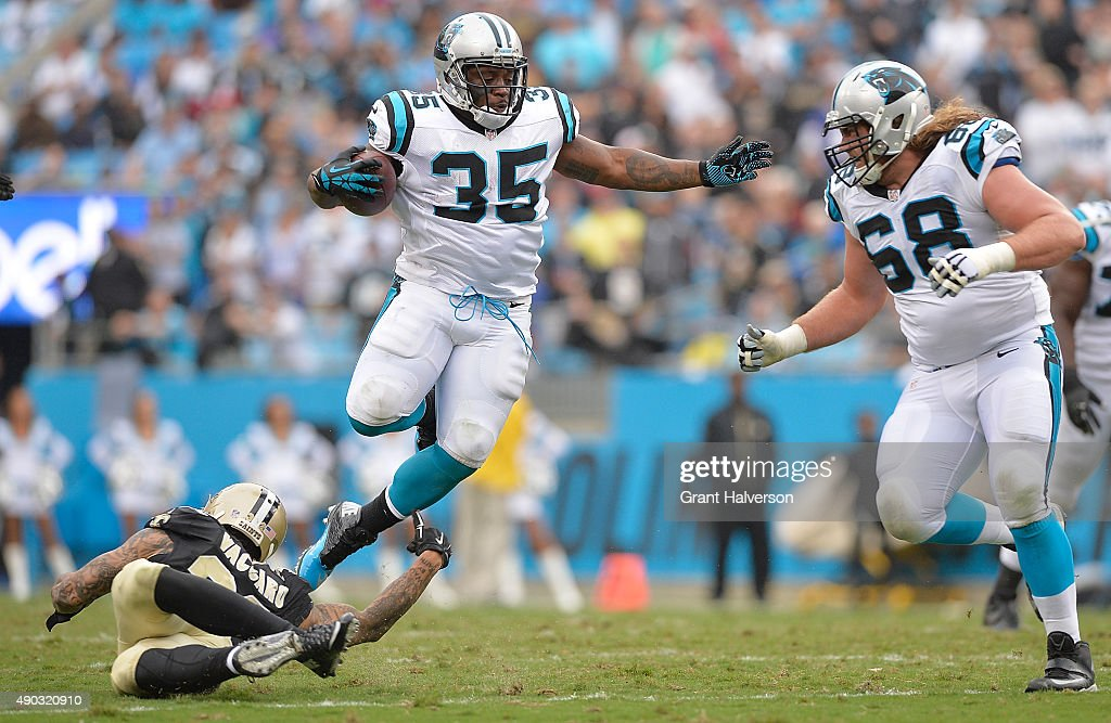 Mike Tolbert of the Carolina Panthers leaps over Kenny Vaccaro of the New Orleans Saints during their game at Bank of America Stadium on September 27...