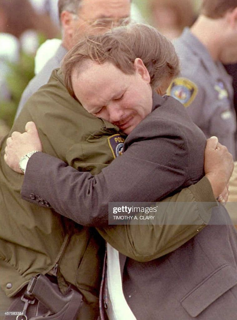 Mike Traynor,the uncle of Ashley Eckles, hugs a police officer after attending a 24 April burial service at the Summit View Cemetery in Guthrie, Oklahoma, for four-year-old Ashley . The child was killed in the 19 April car-bombing of the Alfred P. Murrah Federal Building in Oklahoma City.