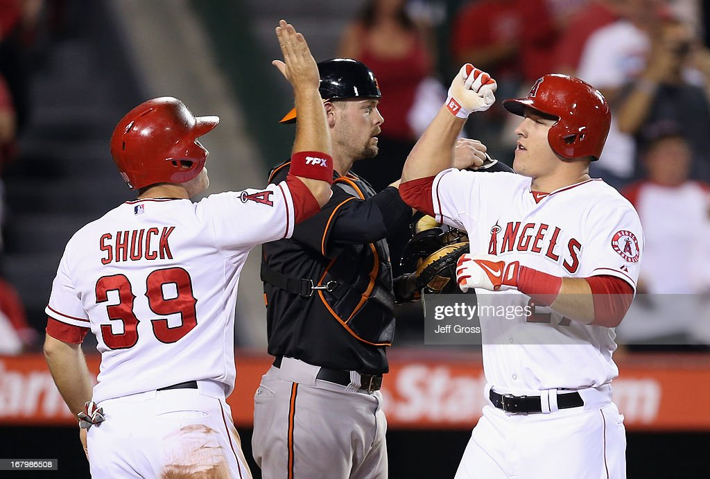 Mike Trout (R) #27 of the Los Angeles Angels of Anaheim is congratulated by J.B. Shuck #39 after hitting a two-run home run in the fifth inning against the Baltimore Orioles at Angel Stadium of Anaheim on May 3, 2013 in Anaheim, California.
