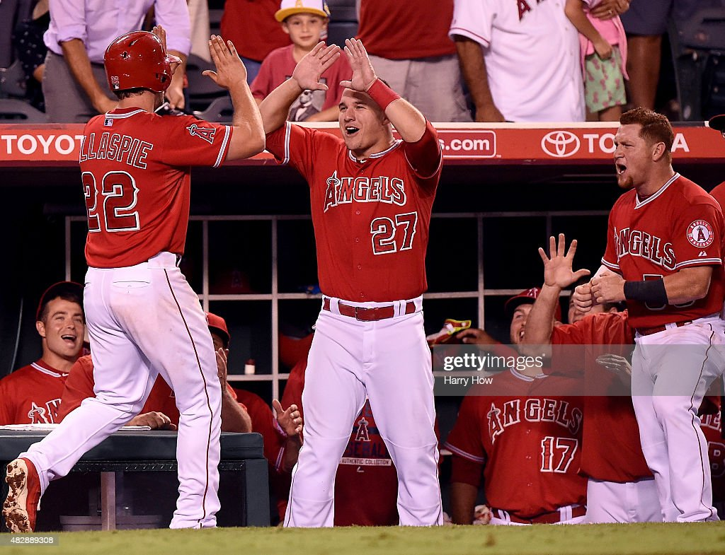 Mike Trout #27 and Kole Calhoun #56 of the Los Angeles Angels react to the two run homerun of Conor Gillaspie #22 to take a 4-3 lead over the Cleveland Indians during the sixth inning at Angel Stadium of Anaheim on August 3, 2015 in Anaheim, California.