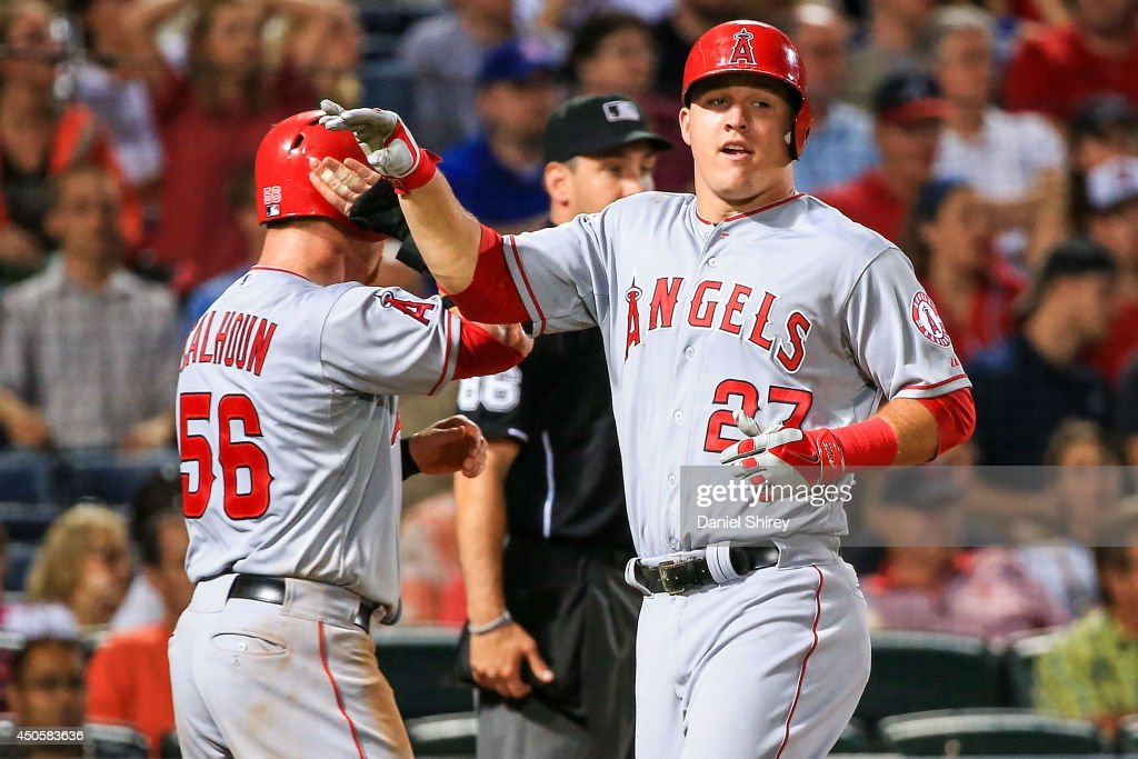 Mike Trout celebrates with Kole Calhoun of the Los Angeles Angels of Anaheim after scoring in the eighth inning against the Atlanta Braves at Turner...