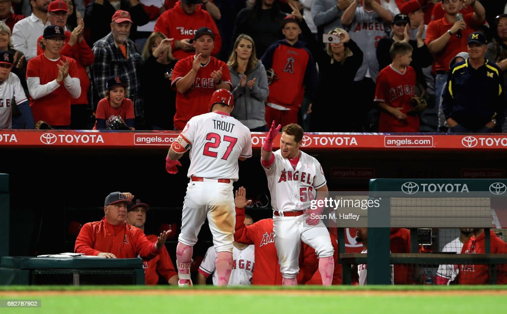 Mike Trout #27 celebrates with Kole Calhoun #56 of the Los Angeles Angels of Anaheim at the dugout after hitting a solo homerun during the seventh inning of a game against the Detroit Tigers at Angel Stadium of Anaheim on May 13, 2017 in Anaheim, California.