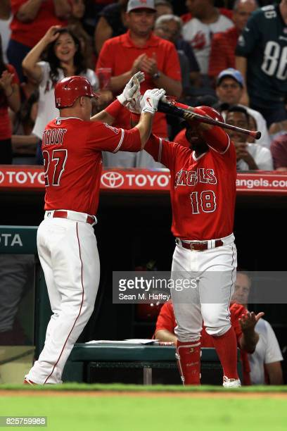 Mike Trout is congratulated at the dugout by Luis Valbuena of the Los Angeles Angels of Anaheim after hitting a tworun homerun during the third...