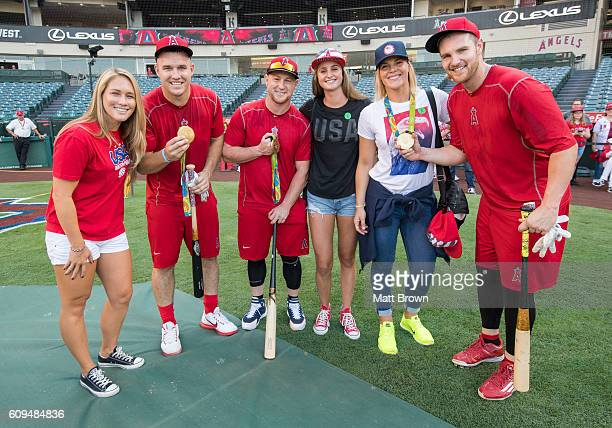 Mike Trout Kole Calhoun and Jett Bandy of the Los Angeles Angels of Anaheim pose with olympic gold medalists from left Courtney Mathewson Maddie...