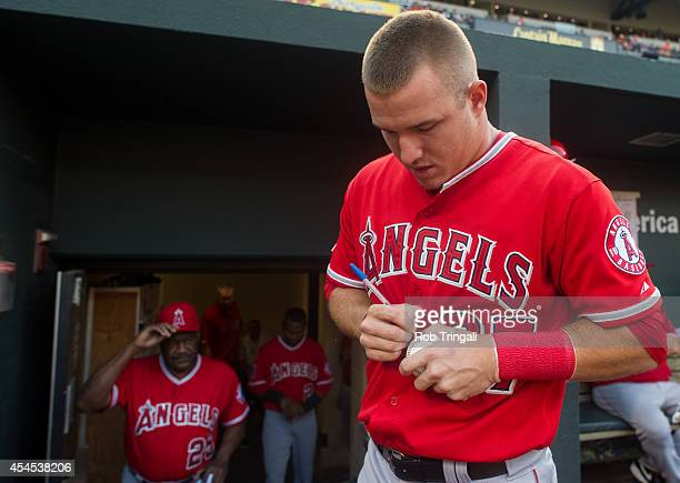 Mike Trout of the Los Angeles Angels autographs a baseball before the game against the Baltimore Orioles at Oriole Park at Camden Yards on July 30...