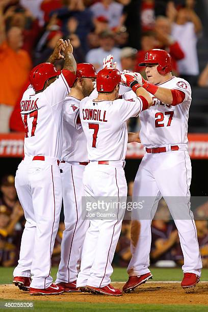 Mike Trout of the Los Angeles Angels celebrates with Collin Cowgill and Howie Kendrick after hitting a grand slam home run to tie the game in the...