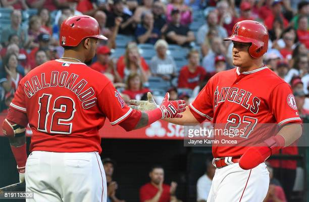 Mike Trout of the Los Angeles Angels gets a hand shake from Martin Maldonado after scoring a run in the first inning against the Washington Nationals...
