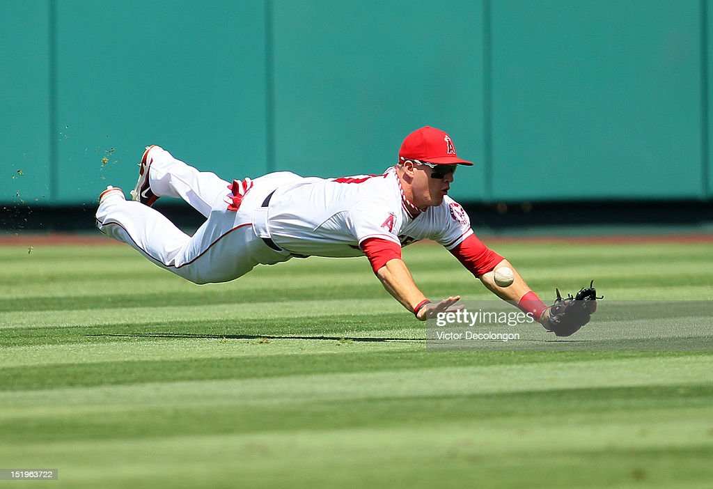 Mike Trout of the Los Angeles Angels of Anaheim can't make the catch at right center field in the third inning against the Oakland Athletics during...