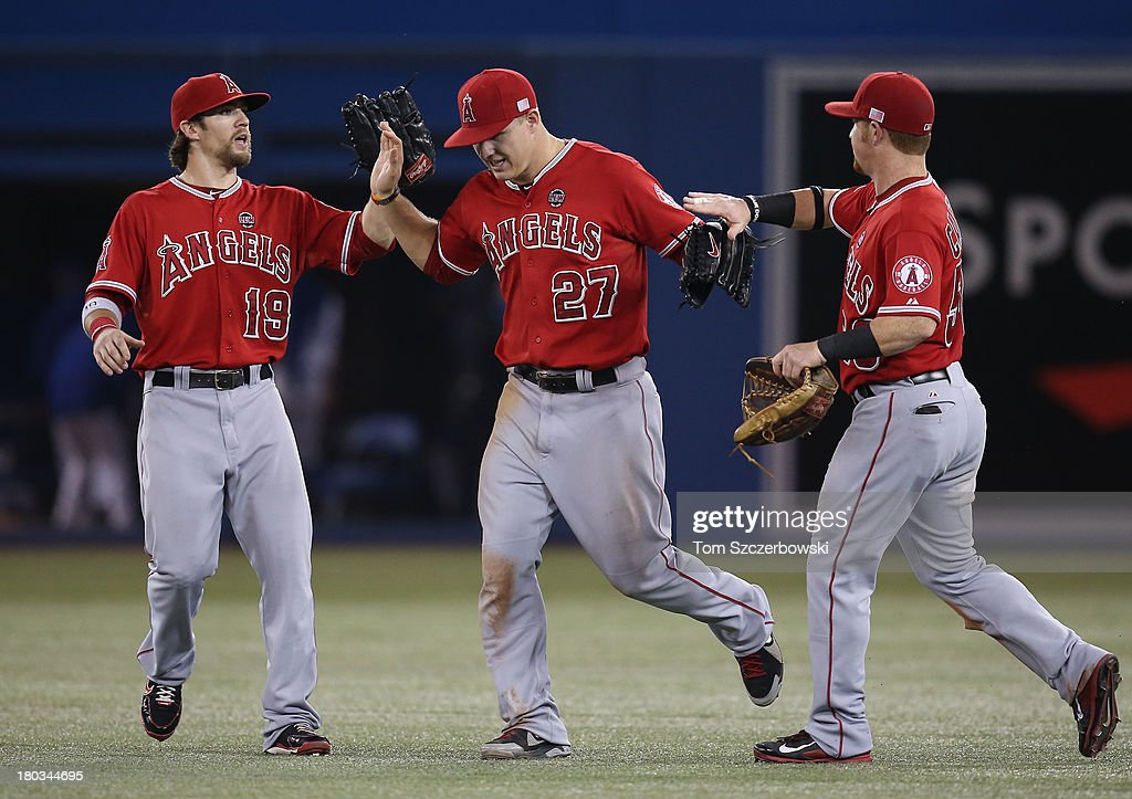 <a gi-track='captionPersonalityLinkClicked' href=/galleries/search?phrase=Mike+Trout&family=editorial&specificpeople=7091306 ng-click='$event.stopPropagation()'>Mike Trout</a> #27 (C) of the Los Angeles Angels of Anaheim celebrates their victory with <a gi-track='captionPersonalityLinkClicked' href=/galleries/search?phrase=Collin+Cowgill&family=editorial&specificpeople=6888953 ng-click='$event.stopPropagation()'>Collin Cowgill</a> #19 and Kole Calhoun #56 during MLB game action against the Toronto Blue Jays on September 11, 2013 at Rogers Centre in Toronto, Ontario, Canada.