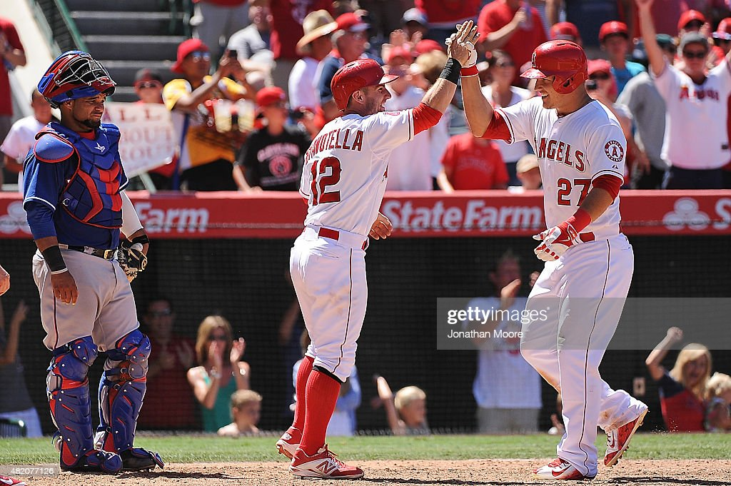 Mike Trout #27 of the Los Angeles Angels of Anaheim celebrates with Johnny Giavotella #12 after hitting a grand slam home run in the sixth inning as Tomas Telis #6 of the Texas Rangers reacts during a game against the Texas Rangers at Angel Stadium of Anaheim on July 26, 2015 in Anaheim, California.