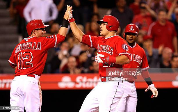 Mike Trout of the Los Angeles Angels of Anaheim celebrates with Johnny Giavotella and Erick Aybar as all three score on Trout's three run home run in...