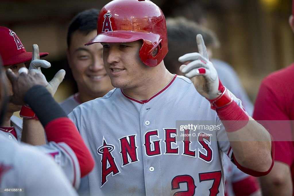 <a gi-track='captionPersonalityLinkClicked' href=/galleries/search?phrase=Mike+Trout&family=editorial&specificpeople=7091306 ng-click='$event.stopPropagation()'>Mike Trout</a> #27 of the Los Angeles Angels of Anaheim celebrates with teammates in the dugout after hitting a home run against the Oakland Athletics during the sixth inning at O.co Coliseum on August 24, 2014 in Oakland, California.