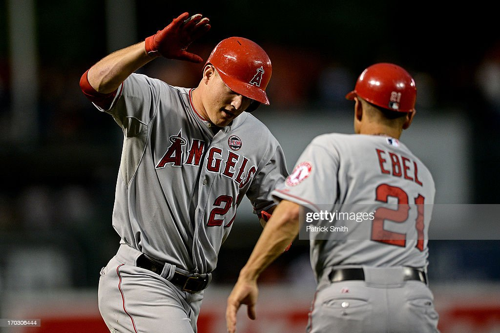 <a gi-track='captionPersonalityLinkClicked' href=/galleries/search?phrase=Mike+Trout&family=editorial&specificpeople=7091306 ng-click='$event.stopPropagation()'>Mike Trout</a> #27 of the Los Angeles Angels of Anaheim celebrates with third base coach Dino Ebel #21 after hitting a solo home run in the third inning against the Baltimore Orioles at Oriole Park at Camden Yards on June 10, 2013 in Baltimore, Maryland.