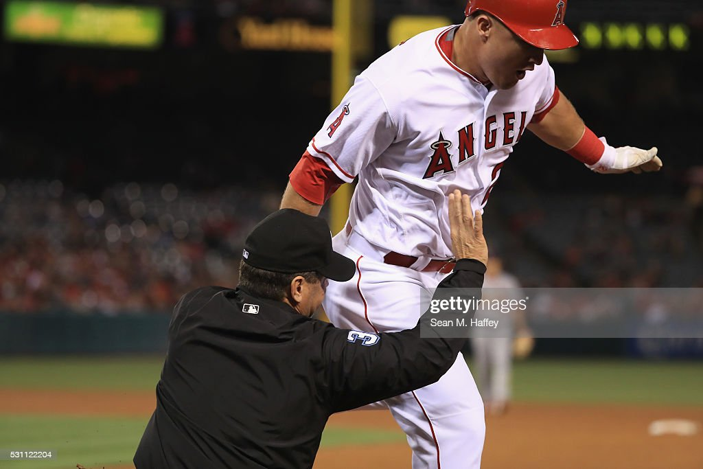 Mike Trout of the Los Angeles Angels of Anaheim collides with first base umpire Rob Drake on an infield single during the fifth inning of a baseball...