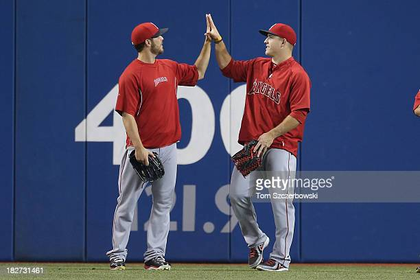 Mike Trout of the Los Angeles Angels of Anaheim compares hand sizes with Michael Kohn during batting practice before MLB game action against the...