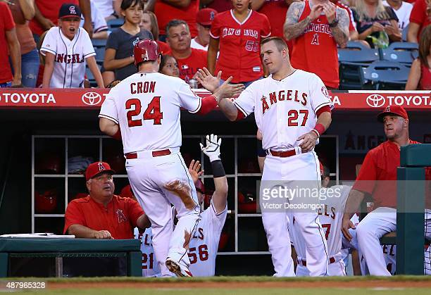 Mike Trout of the Los Angeles Angels of Anaheim congratulates teammate CJ Cron as Cron enters the dugout after scoring in the second inning against...