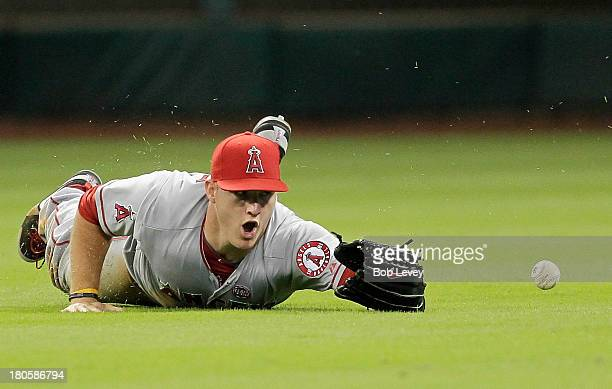 Mike Trout of the Los Angeles Angels of Anaheim dives but can't make the catch on a shallow fly ball hit by Matt Dominguez of the Houston Astros in...