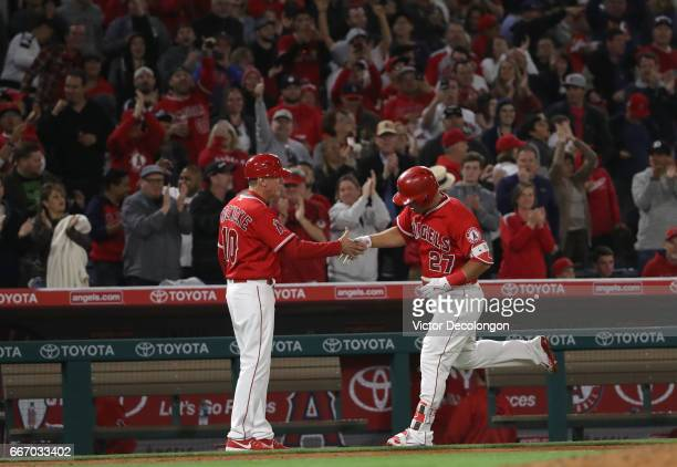 Mike Trout of the Los Angeles Angels of Anaheim gets a handshake from third base coach Ron Roenicke after Trout hit a tworun homerun during the...