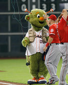 Mike Trout of the Los Angeles Angels of Anaheim has some fun with Houston Astros mascot Orbit at Minute Maid Park on September 2 2014 in Houston Texas