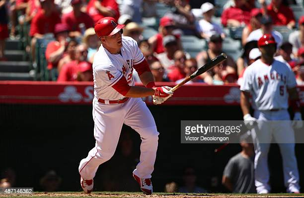 Mike Trout of the Los Angeles Angels of Anaheim hits a sacrifice fly to center in the second inning as teammate Albert Pujols watches from the ondeck...