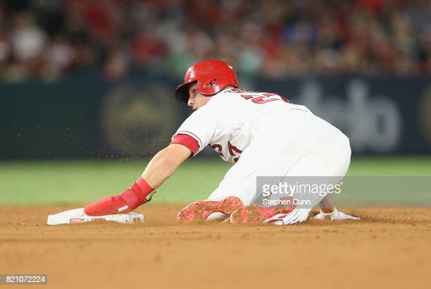 Mike Trout of the Los Angeles Angels of Anaheim holds onto second base with his hand in its protective glove as he slides in with a stolen base in...