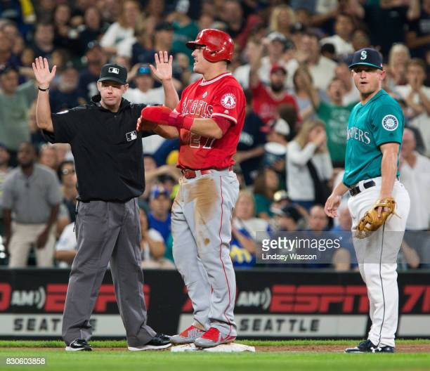 Mike Trout of the Los Angeles Angels of Anaheim is called safe at third on a single by Albert Pujols as Kyle Seager of the Seattle Mariners reacts in...