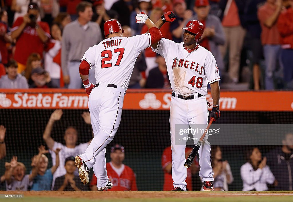 Mike Trout #27 of the Los Angeles Angels of Anaheim is congratulated by Torii Hunter #48 after hitting a solo home run in the eighth inning against the Baltimore Orioles at Angel Stadium of Anaheim on July 6, 2012 in Anaheim, California. The Orioles defeated the Angels 3-2.
