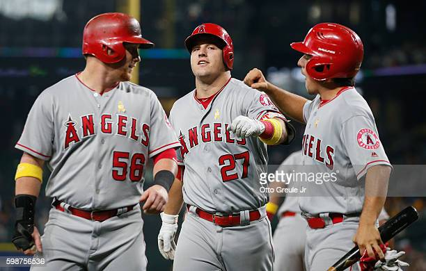 Mike Trout of the Los Angeles Angels of Anaheim is congratulated by Kole Calhoun and the batboy after hitting a threerun homer against the Seattle...