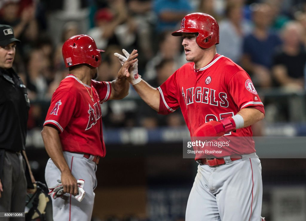 Mike Trout #27 of the Los Angeles Angels of Anaheim is greeted by Ben Revere #25 of the Los Angeles Angels of Anaheim after both scored on a double by Albert Pujols #5 of the Los Angeles Angels of Anaheim off of relief pitcher Tony Zych #55 of the Seattle Mariners during the eighth inning of a game at Safeco Field on August 12, 2017 in Seattle, Washington.