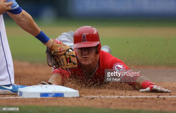 Mike Trout of the Los Angeles Angels of Anaheim is tagged out by Danny Valencia of the Kansas City Royals as he tries to advance to third on a Albert...