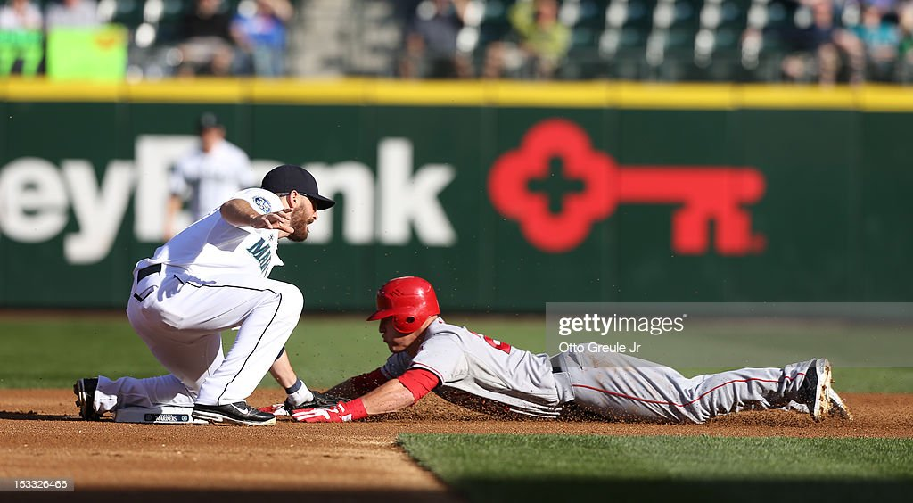 Mike Trout #27 of the Los Angeles Angels of Anaheim is tagged out on a steal attempt by second baseman Dustin Ackley #13 of the Seattle Mariners at Safeco Field on October 3, 2012 in Seattle, Washington.