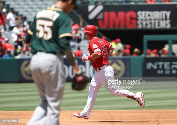 Mike Trout of the Los Angeles Angels of Anaheim jogs to third base after hitting a solo homerun off of pitcher Sean Manaea of the Oakland Athletics...