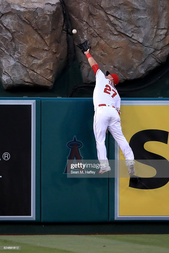 Mike Trout of the Los Angeles Angels of Anaheim leaps unsuccessfully to catch this home run by Mike Moustakas of the Kansas City Royals during the...