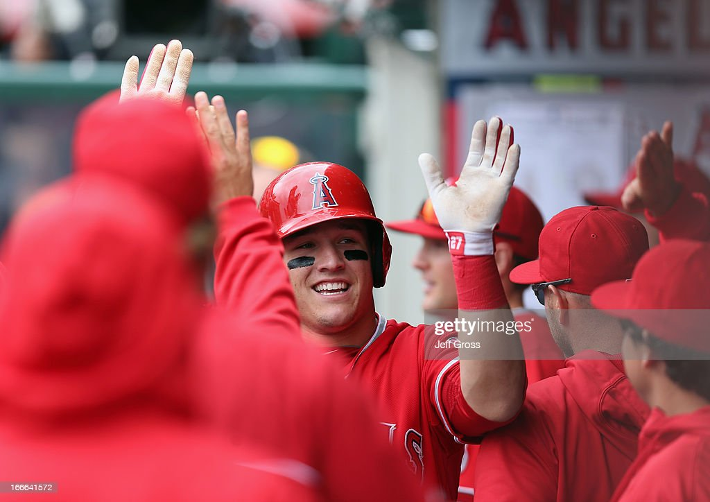 <a gi-track='captionPersonalityLinkClicked' href=/galleries/search?phrase=Mike+Trout&family=editorial&specificpeople=7091306 ng-click='$event.stopPropagation()'>Mike Trout</a> #27 of the Los Angeles Angels of Anaheim receives high fives in the dugout after scoring a run in the first inning against the Houston Astros at Angel Stadium of Anaheim on April 14, 2013 in Anaheim, California.