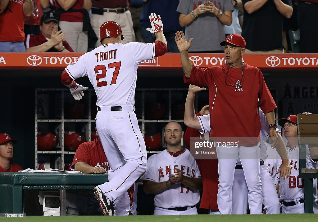 Mike Trout #27 of the Los Angeles Angels of Anaheim receives high fives in the dugout after hitting a two-run home run in the fifth inning against the Baltimore Orioles at Angel Stadium of Anaheim on May 3, 2013 in Anaheim, California. The Angels defeated the Orioles 4-0.