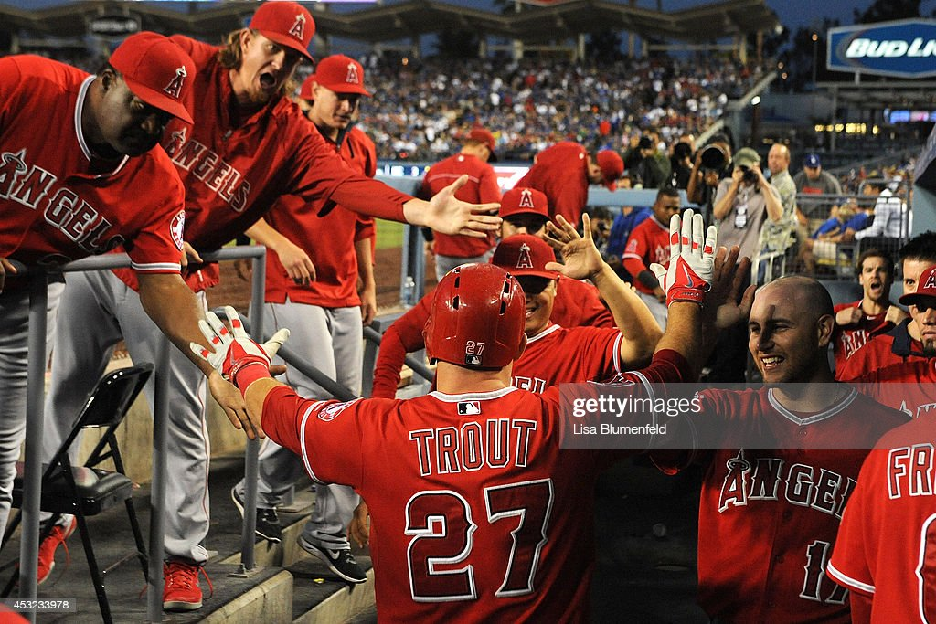 Mike Trout of the Los Angeles Angels of Anaheim returns to the dugout after scoring in the third inning against the Los Angeles Dodgers at Dodger...