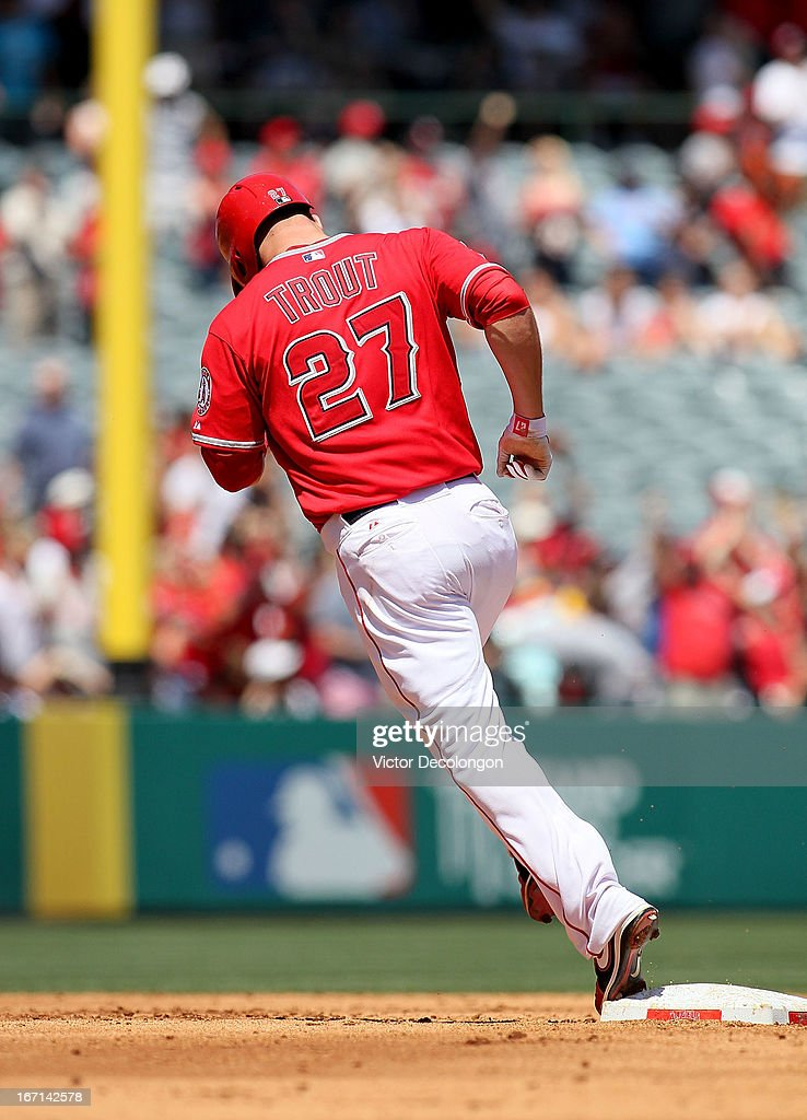 Mike Trout #27 of the Los Angeles Angels of Anaheim rounds second base after hitting a grand slam home run against pitcher Rick Porcello #21 of the Detroit Tigers (not in photo) in the first inning of their MLB game at Angel Stadium of Anaheim on April 20, 2013 in Anaheim, California. It was Trout's first career grand slam. The Angels defeated the Tigers 10-0.