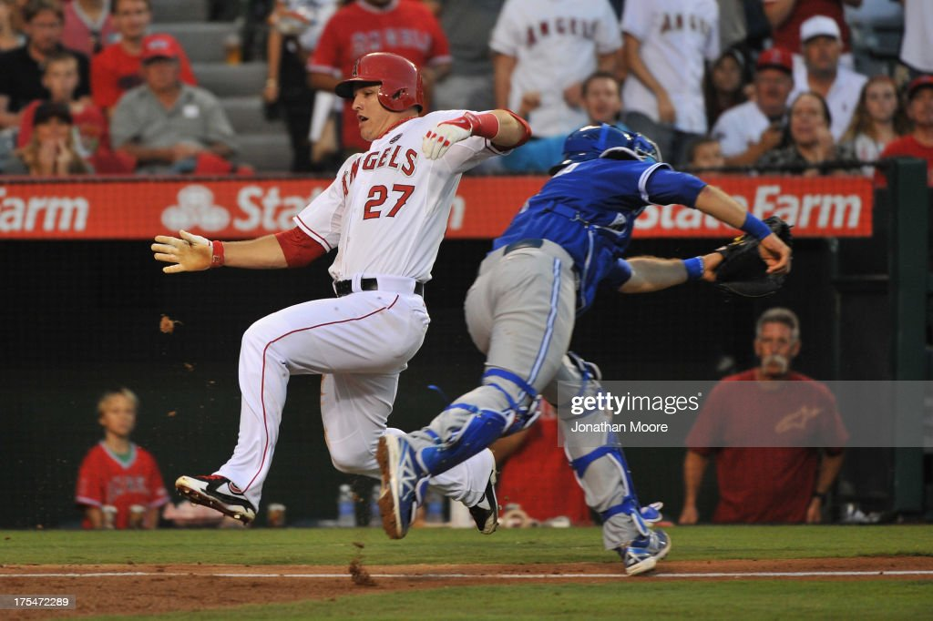 <a gi-track='captionPersonalityLinkClicked' href=/galleries/search?phrase=Mike+Trout&family=editorial&specificpeople=7091306 ng-click='$event.stopPropagation()'>Mike Trout</a> #27 of the Los Angeles Angels of Anaheim scores past <a gi-track='captionPersonalityLinkClicked' href=/galleries/search?phrase=J.P.+Arencibia&family=editorial&specificpeople=4959430 ng-click='$event.stopPropagation()'>J.P. Arencibia</a> #9 of the Toronto Blue Jays on an RBI single hit by Howie Kendrick #47 (not pictured) at the bottom of the fourth at Angel Stadium of Anaheim on August 3, 2013 in Anaheim, California.