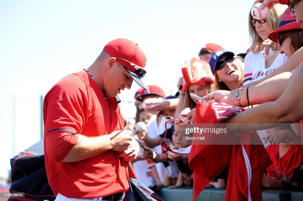 Mike Trout of the Los Angeles Angels of Anaheim signs autographs for some fans prior to a game against the Chicago Cubs during a spring training game...
